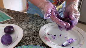 Una donna in guanti dipinge le uova stock footage