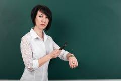 Una donna guarda tramite una lente d'ingrandimento sull'orologio, su una lavagna come fondo, su un concetto di istruzione e sull' Immagini Stock