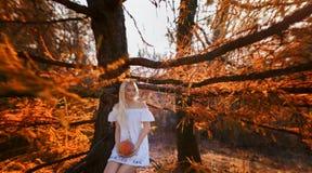 Una donna ha condito in un vestito bianco con le tenute del ricamo una zucca Fotografia Stock
