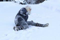 Una donna ha slittato e caduto sulla strada dell'inverno fotografia stock