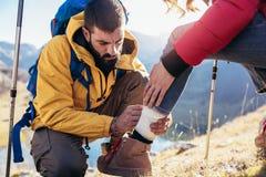 Una donna ha storto la sua caviglia mentre fa un'escursione, il suo amico usa la cassetta di pronto soccorso fotografia stock
