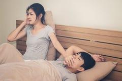 Una donna ha un fastidio all'uomo che ama dormire alto russando immagine stock