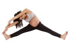 Una donna incinta allunga molto le sue gambe prima dell'esercizio. Immagine Stock