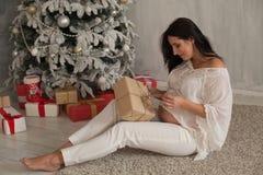 Una donna incinta che si siede dall'albero di Natale apre i regali di Natale fotografia stock
