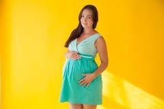 Una donna incinta prima del fondo di giallo di parto Fotografie Stock Libere da Diritti