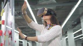 Una donna indossa i vetri e gli impianti di VR con l'organizzazione del progetto su un bordo stock footage