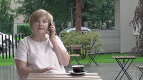 Una donna invecchiata graziosa sta parlando emozionalmente sopra il telefono È spiegare, rispondente video d archivio
