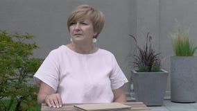 Una donna invecchiata graziosa sta sedendosi meditatamente all'aperto nel terrazzo e sta guardando intorno stock footage
