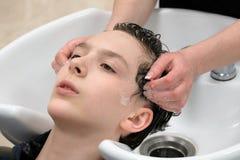 Una donna lava una testa del ` s del giovane in un salone di bellezza Le mani femminili del parrucchiere insaponano i capelli del fotografia stock libera da diritti