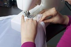 Una donna lavora ad una macchina per cucire Cuce le tende sulla finestra Fotografia Stock