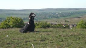 Una donna lussuosa in una passeggiata nera del bordo sopra il prato archivi video