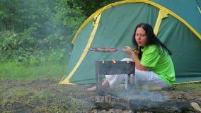 Una donna in una maglietta verde sta sedendosi nella foresta sui precedenti di una tenda, il fuoco sta soffiando nel suo addetto  archivi video