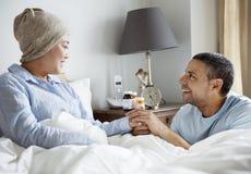 Una donna malata a letto con il suo partner immagini stock