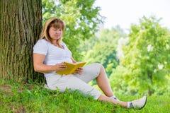 Una donna matura di 50 anni che legge un libro Fotografie Stock Libere da Diritti