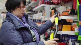 Una donna matura sceglie una spazzola con la ruspa spianatrice nel supermercato archivi video