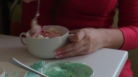 Una donna mescola il formaggio cremoso con colorante alimentare Prima di dare coloritura uniforme Crema di coloritura per lubrifi video d archivio