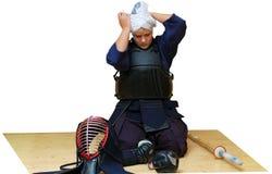 Una donna mette sopra l'uniforme di kendo Fotografie Stock