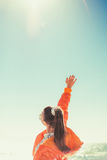 Una donna nei precedenti del mare estrae la sua mano al cielo Vista posteriore Immagini Stock Libere da Diritti