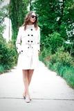 Una donna o una ragazza in un cappotto sta stando su una banchina fra gli alberi immagini stock libere da diritti
