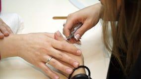 Una donna ottiene lei le unghie sistemate e pulite prima dell'ottenere le sue unghie dipinte per il suo manicure Manicure con i t archivi video
