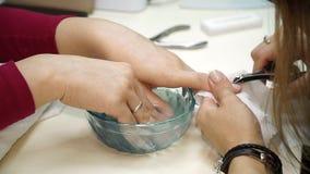 Una donna ottiene lei le unghie sistemate e pulite prima dell'ottenere le sue unghie dipinte per il suo manicure Manicure con i t stock footage