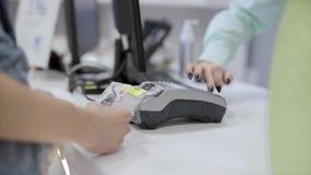 Una donna paga un acquisto in un deposito con una carta assegni facendo uso di un terminale le mani della donna del primo piano c stock footage