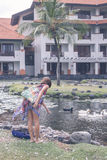 Una donna in pareo alimenta le oche e le papere grige del ritardo sul lago vicino all'albergo di lusso nel DUA di Nusa, isola tro Immagine Stock