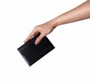 Una donna passa a tenuta un walletcase di cuoio nero, tasca per il passaporto, carta di credito sulla vista superiore desktable b Fotografia Stock