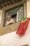 Una donna più anziana celebra la vittoria di calcio appendendo la bandiera del Portoghese fuori la finestra di Tomar, Portogallo Fotografia Stock Libera da Diritti
