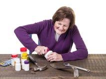 Una donna più anziana che lotta per aprire una bottiglia della medicina Immagine Stock