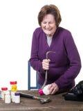 Una donna più anziana che lotta per aprire una bottiglia della medicina Immagini Stock Libere da Diritti