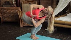 Una donna più anziana fa bene la respirazione durante l'esercizio di yoga nella sala archivi video