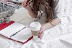 Una donna più anziana scrive un piano del giorno su un calendario Accanto è una tazza di tè Concetto di affari Fine in su immagine stock libera da diritti