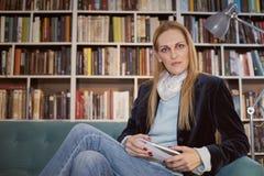 una donna, posando, esaminando macchina fotografica, tenente rivista Scaffale in pieno dei libri dietro sfuocato Immagini Stock