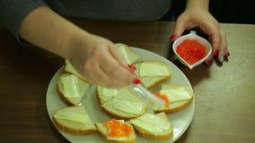 Una donna prende il caviale rosso da un cucchiaio di Iornitsa e spande il burro sulle canape con burro archivi video