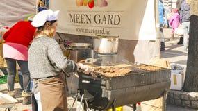 Una donna prepara i kebab norvegesi tradizionali su un a calore ridotto Immagine Stock