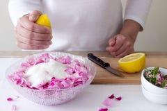Una donna prepara l'inceppamento dalle rose, ingredienti per inceppamento dalle rose Stile rustico fotografie stock libere da diritti