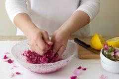 Una donna prepara l'inceppamento dalle rose, ingredienti per inceppamento dalle rose Stile rustico fotografia stock libera da diritti