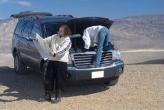 Una donna prova a riparare un'automobile mentre il marito legge un programma Fotografie Stock