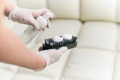 Una donna pulisce il sofà di cuoio con una spazzola e un detersivo fotografie stock libere da diritti