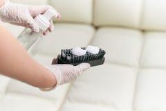 Una donna pulisce il sofà di cuoio con una spazzola e un detersivo fotografia stock libera da diritti