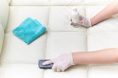 Una donna pulisce il sofà di cuoio con una spazzola e un detersivo immagini stock libere da diritti