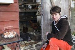 Una donna rurale si inginocchia fuori della sua gabbia di pollo Immagine Stock Libera da Diritti