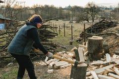 Una donna rurale spara un legno dell'albero di cenere per la raccolta per l'inverno con un'ascia immagine stock libera da diritti