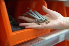 Una donna sceglie il perno-chiodo in un deposito delle merci della costruzione fotografie stock