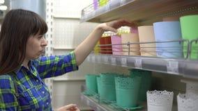 Una donna sceglie un vaso di fiore in un supermercato video d archivio