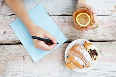 Una donna scrive un articolo e beve il tè caldo Vista superiore Il concentrato Fotografie Stock Libere da Diritti