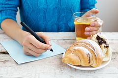 Una donna scrive un piano e beve il tè caldo Il concetto di alimento, w Fotografia Stock Libera da Diritti