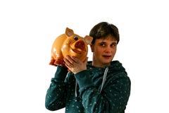 Una donna scuote un porcellino salvadanaio e sente se i soldi sono in  fotografie stock libere da diritti