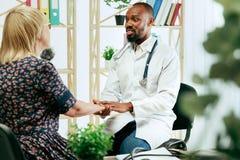 Una donna senior che visita un terapista alla clinica immagine stock libera da diritti